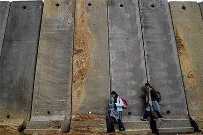 Dos niñas palestinas circulan cerca de Ramala ante el muro de separación levantado por Israel.