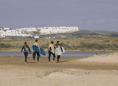Surfistas pasean frente al paraje de El Palmar donde se proyectan los apartahoteles.