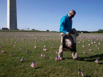 Un hombre cruza con un retrato de su madre, fallecida por covid, entre las miles de banderas colocadas junto a la base del obelisco de Washington como homenaje a las víctimas del coronavirus, el pasado 22 de septiembre.