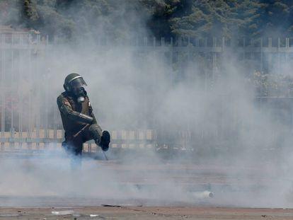 Un miembro de las fuerzas de seguridad chilenas golpea un bote de gas este viernes.