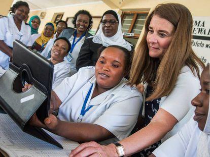 La enfermera Chesca Mbilinyi y Melinda Gates prueban un nuevo sistema digital para clasificar historiales de pacientes en el centro de salud de Magomeni de Dar es Salaam, en Tanzania, en junio de 2016.