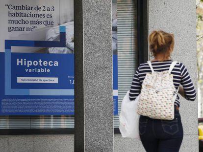 Una mujer pasa por delante de un anuncio de hipotecas en Madrid, en una imagen de archivo.