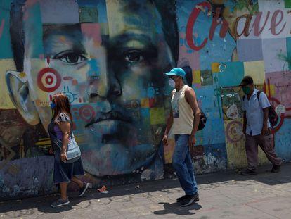 Tres personas con tapabocas caminan frente a un mural de Hugo Chávez, el 3 de marzo en Caracas, Venezuela.