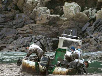 Marineros gallegos recogen fuel del <i>Prestige</i> en su barca junto a las islas Cíes.