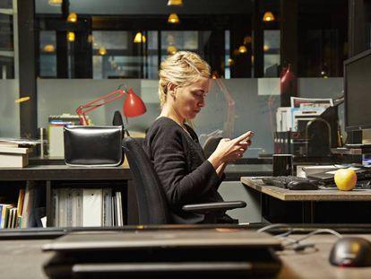 Una mujer consulta su teléfono en el trabajo.