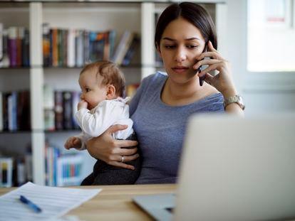 Una mujer teletrabaja con su bebé en brazos.