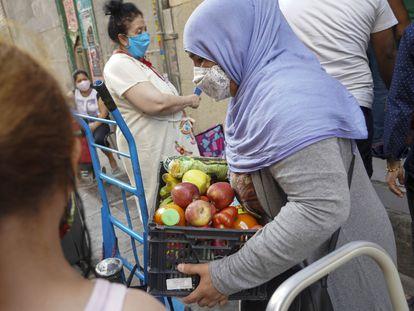 Entrega de alimentos a personas necesitadas en la Asociación Valiente Bangla del barrio de Lavapiés.