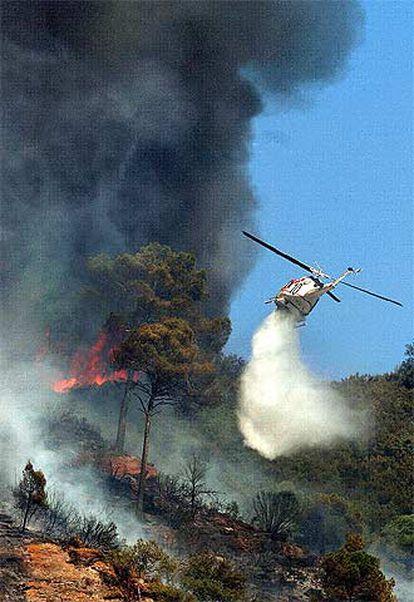 Un helicóptero vierte agua sobre las llamas durante las labores de extinción del incendio junto a la autopista AP-, en Martorell.
