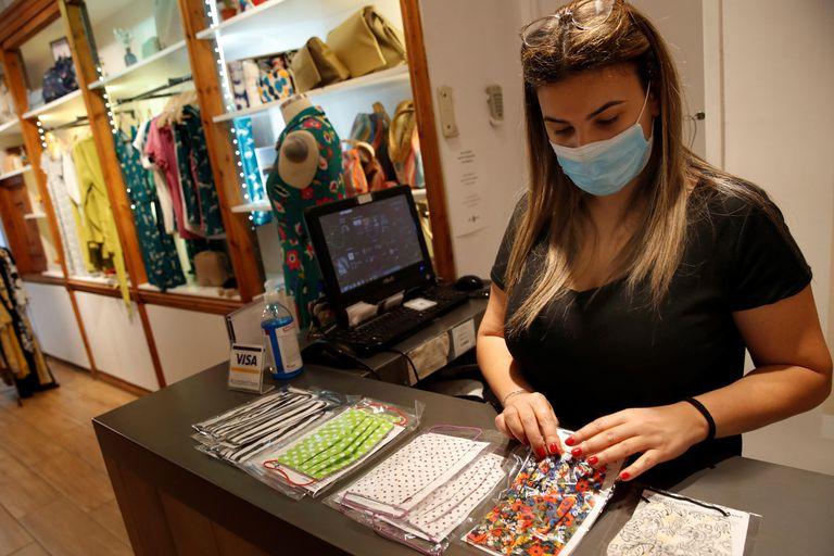 Una empleada de una tienda de Barcelona coloca unas mascarillas.