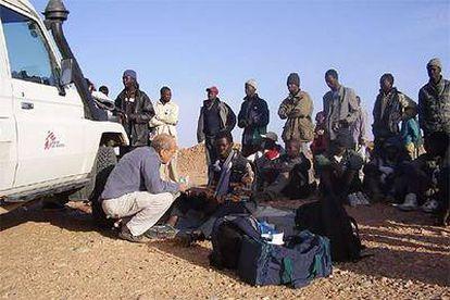 Un miembro de Médicos Sin Fronteras atiende a unos subsaharianos deportados por Marruecos al desierto en la frontera con Argelia.