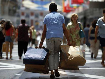 Un viandante con varias bolsas de tiendas en la calle de Preciados (Madrid).