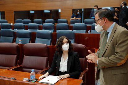El diputado del PP Alfonso Carlos Serrano habla con Isabel Díaz Ayuso, durante el pleno de este jueves en la Asamblea de Madrid.