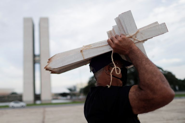 A protester holds up wooden crosses at a protest in Brazil's Congress against Jair Bolsonaro's management of the pandemic, on March 19.