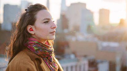 Una mujer, con un auricular inalámbrico.