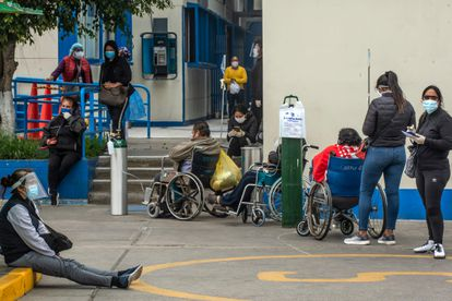 Several people wait outside a hospital in Lima, Peru, in May 2020.