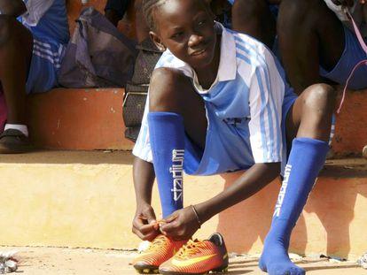 Una joven jugadora de fútbol gambiana se ata las botas.