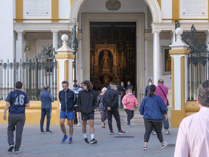 Fieles en la puerta de la basílica de La Macarena, en Sevilla.