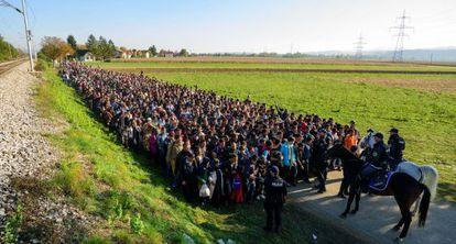 Policías frente a los emigrantes que acababan de cruzar la frontera entre Croacia y Eslovenia, en octubre de 2015.
