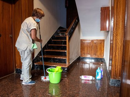 Una empleada realiza labores de limpieza en el portal de un edificio en Toledo.