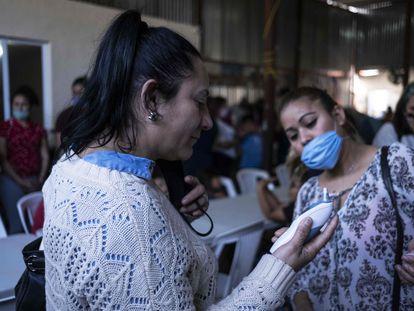 Una mujer se toma la temperatura en un asilo para migrantes de Tijuana.