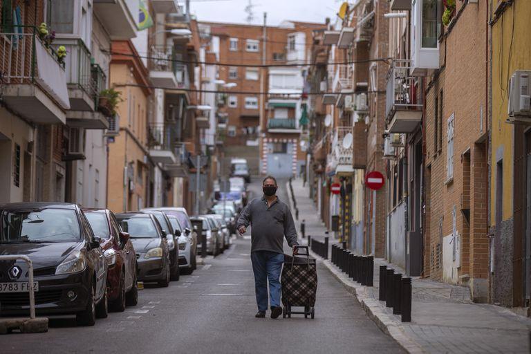 Un hombre con carrito de la compra baja por una calle del barrio Zofío, una de las 37 zonas confinadas en Madrid.