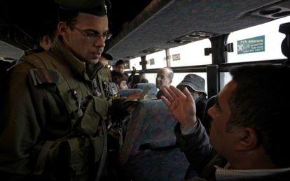 Un soldado israelí pide la documentación a un palestino en un autobús, en el puesto de control de Hizme, antes de entrar en Jerusalén.