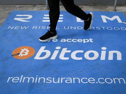 Un hombre camina sobre una alfombra con el logo del bitcoin durante la conferencia sobre la criptomoneda celebrada este mes en Miami.