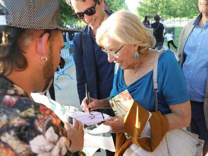 La alcaldesa de Madrid Manuela Carmena firmando un autógrafo en una de las pancartas de su candidatura ayer a orillas del Manzanares (Madrid).