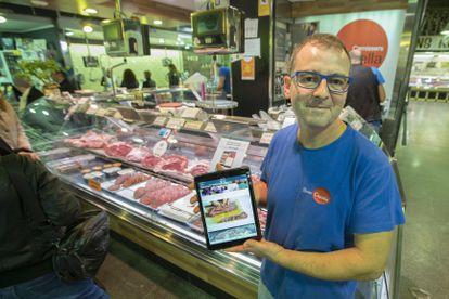 Un carnicero de Barcelona muestra la aplicación para la venta en internet, en 2017.