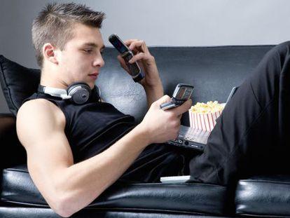 Un joven tumbado en un sofá utilizando un teléfono móvil, un ordenador portátil y un MP4.