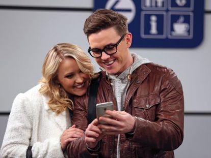 Dos de los actores de la comedia americana 'Young & Hungry' (2014), dando utilidad a su smarphone en un aeropuerto.