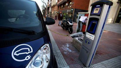 Un vehículo eléctrico enchufado a un punto de carga en el centro de Madrid.