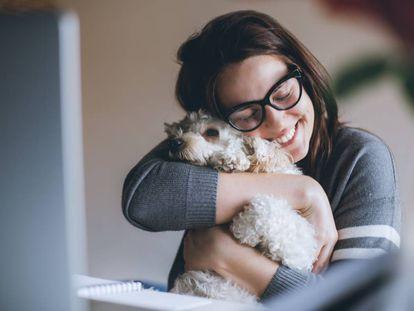 Una mujer abraza a su mascota.