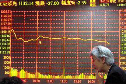 Un inversor chino en Shanghai, ante un tablero electrónico que muestra las cotizaciones de la Bolsa.