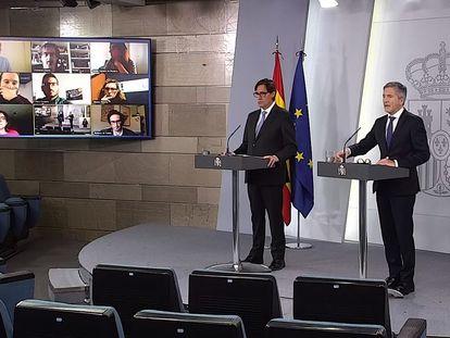 Rueda de prensa virtual ofrecida por el ministro de Sanidad, Salvador Illa (izquierda), y el ministro del Interior, Fernando Grande-Marlaska. En la pantalla, los periodistas autorizados a preguntar. EFE/ La Moncloa