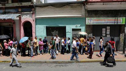 Vecinos de Caracas, Venezuela, haciendo cola para poder comprar alimentos en un supermercado.