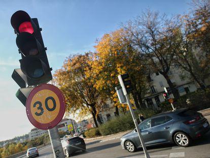 Varios coches circulan al lado de una señal de tráfico en una vía de la capital el mismo día en que se aprobó la reducción de la velocidad hasta 20 kilómetros por hora en las ciudades y la pérdida de seis puntos por usar el móvil, en Madrid, el pasado 10 de noviembre.