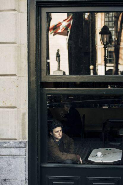 Jon Viar, en el Café Iruña de Bilbao. En la cristalera se refleja la estatua de Sabino Arana, fundador del PNV, y la ikurriña en la sede del partido.
