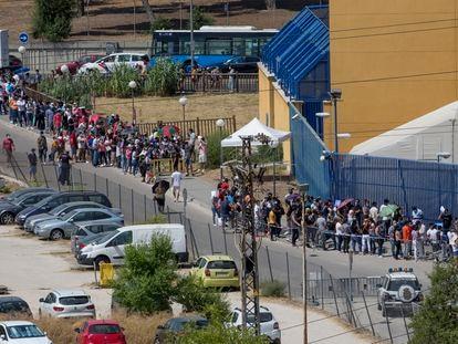 Cola de ciudadanos extranjeros frente a la comisaría de extranjería de Aluche, en Madrid, este jueves. / SANTI BURGOs