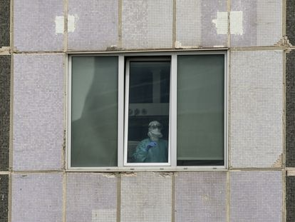 Un médico de UCI en el Hospital La Paz, en Madrid, a través de una ventana.