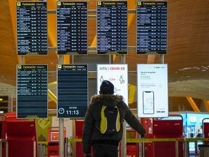 Un pasajero en el panel de salidas del aeropuerto de Barajas (Madrid).