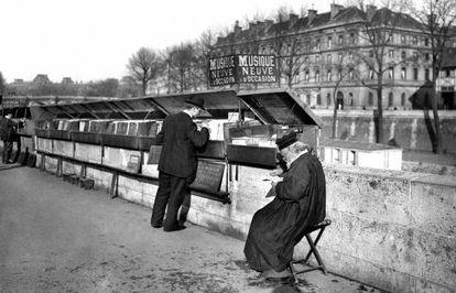 Un 'bouquiniste' del Sena, en 1910: el consistorio de París les ayuda a mantener el negocio cultural.