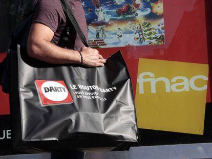 Un hombre pasa con una bolsa de Darty frente a una tienda de Fnac en Niza