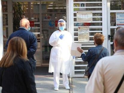 Una sanitaria sale a atender a las personas que hacen cola en un centro de salud en Vicálvaro (Madrid), este lunes.