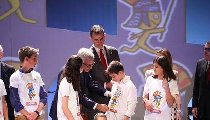 Felipe VI y el alcalde de Tarragona con niños que lucen la mascota de los juegos en la camiseta.