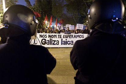 """La Polícia Nacional contra la marcha en Santiago de Compostela contra la visita del Papa a la capital gallega. En la pancarta: """"No te esperamos. Galicia laica""""."""