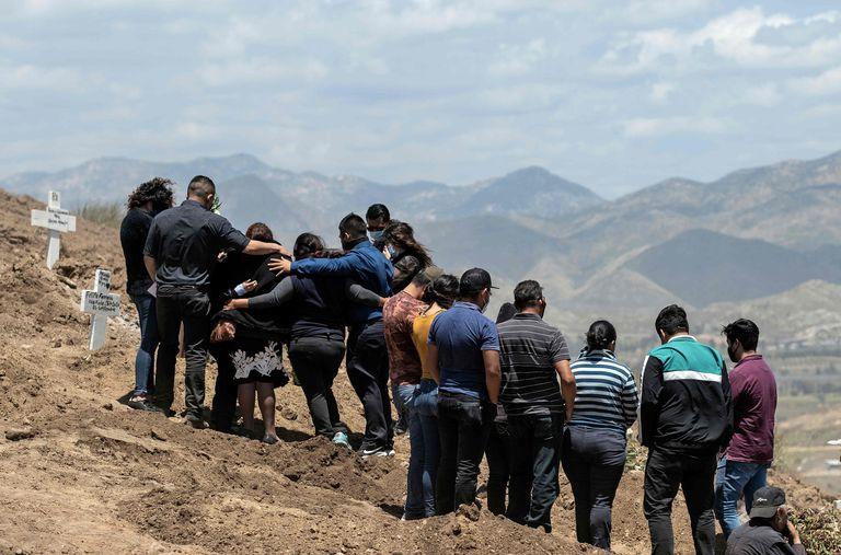 Dos familias acuden al entierro de dos víctimas de coronavirus en Tijuana, Baja California, en mayo.