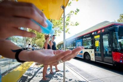 Un usuario se lava las manos con gel hidroalcohólico antes de subir a un autobús urbano de Barcelona.