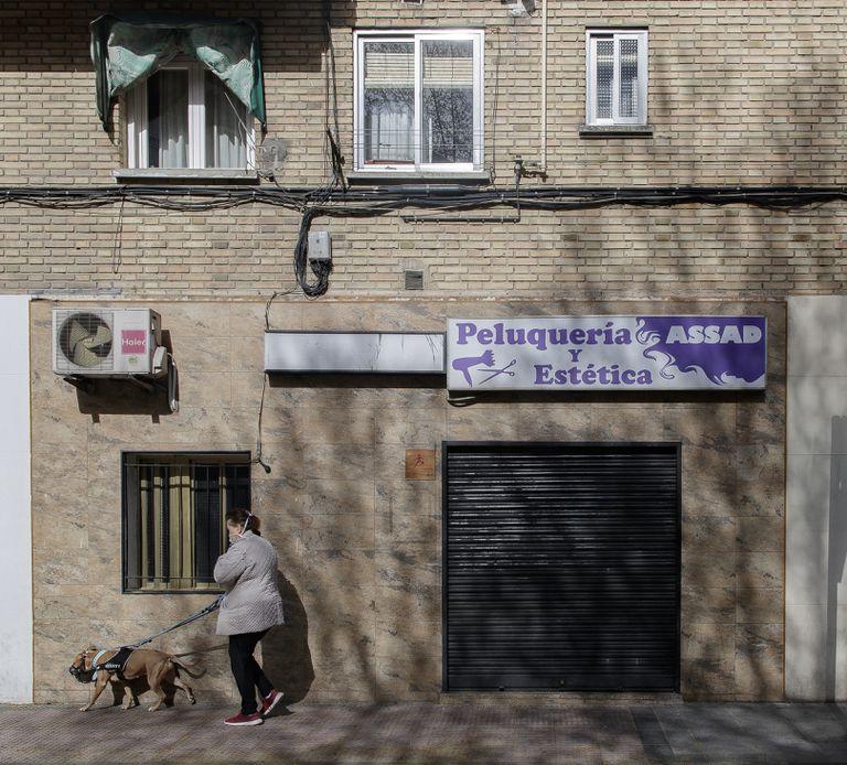 Una mujer pasea a un perro cerca de una peluquería cerrada durante el primer día laborable desde que se decretó el estado de alarma en todo el territorio nacional a consecuencia del coronavirus, en Alcorcón (Madrid), a 16 de marzo de 2020.
