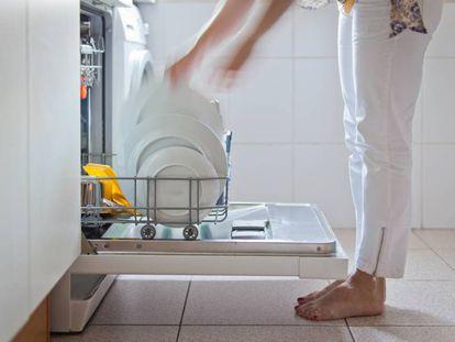 Una mujer retira los platos del lavavajillas. GETTY